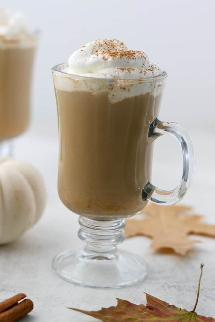 Pumpkin spice latte in a glass mug with fall leaves