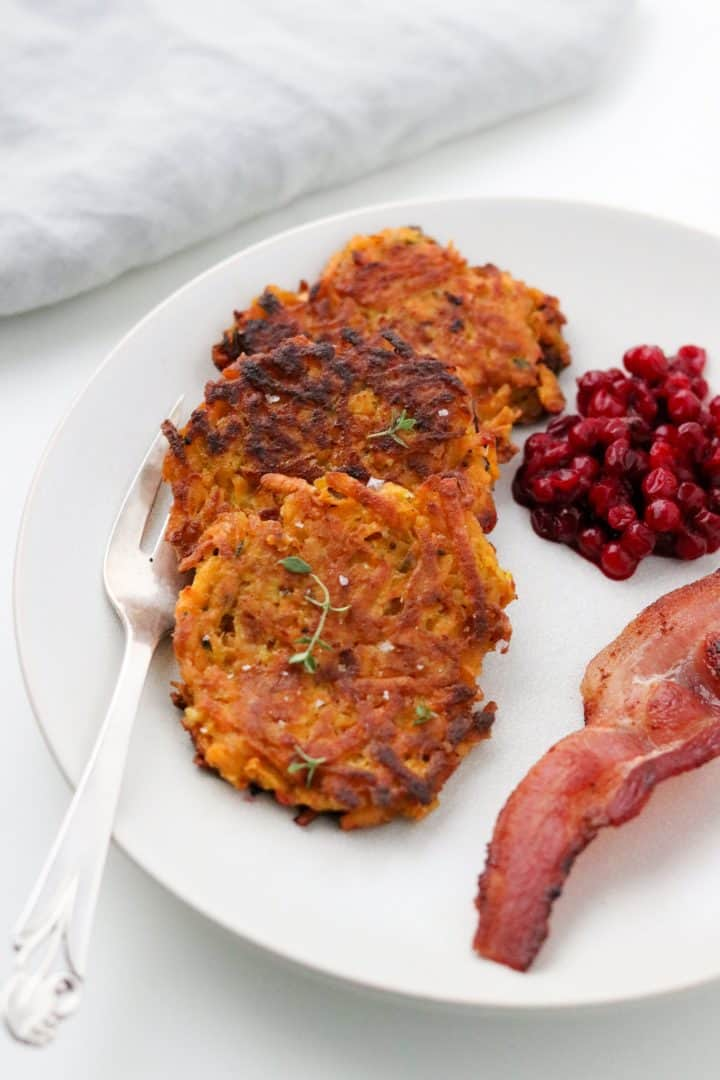 Crispy Sweet Potato Pancakes with Lingonberry Preserves and Bacon on a plate