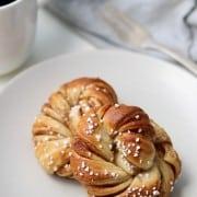 Two Swedish cinnamon buns on a plate next to a mug of coffee, fork and napkin