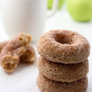 Close up of stack of three apple donuts next to a cup of coffee and apples