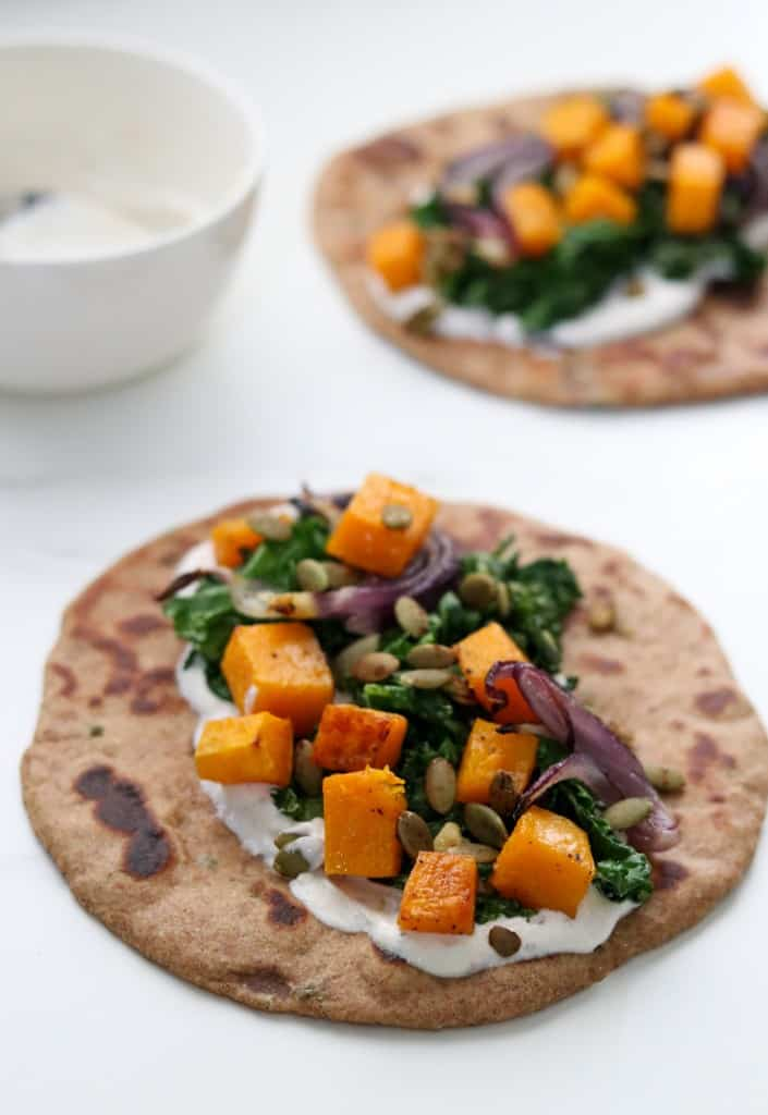 Flatbread topped with a creamy sauce and vegetables
