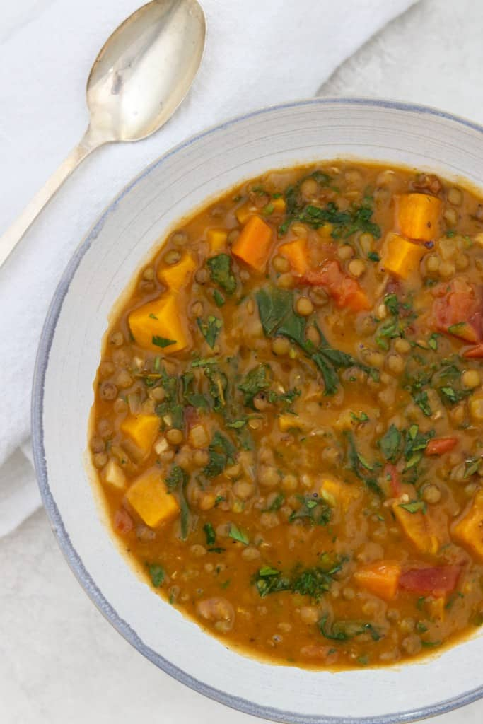 Close up of a bowl of Hearty Lentil Soup with Roasted Butternut Squash, Kale and Bacon next to a spoon and napkin