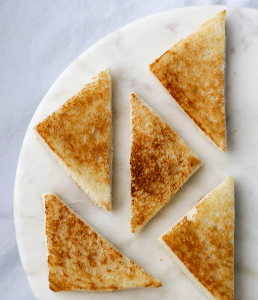 Small triangles of toast on a marble surface