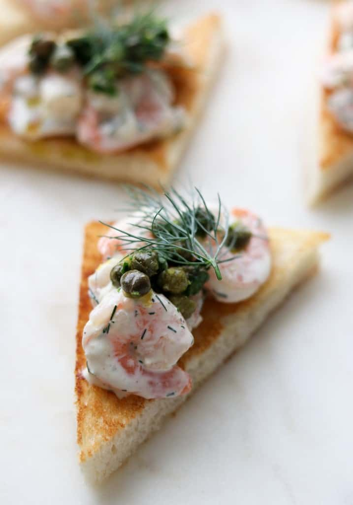 Close up of toast triangle topped with creamy shrimp salad, capers and dill
