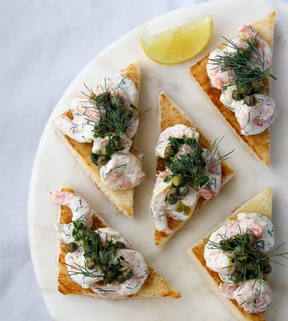 Toast triangles topped with shrimp salad, capers and dill next to lemon wedges