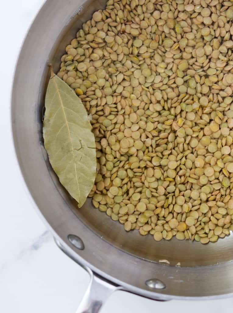 Lentils, water and a bay leaf in a pan
