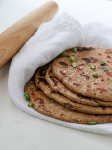 Flatbreads stacked on a towel next to a rolling pin