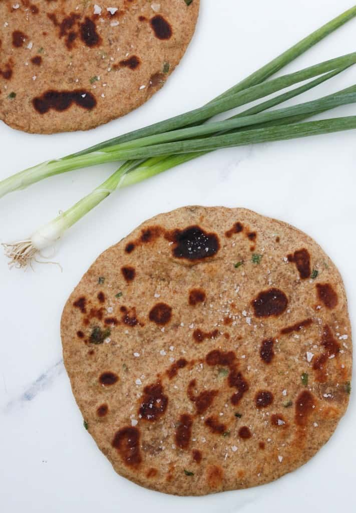 Flatbreads on a countertop with scallions
