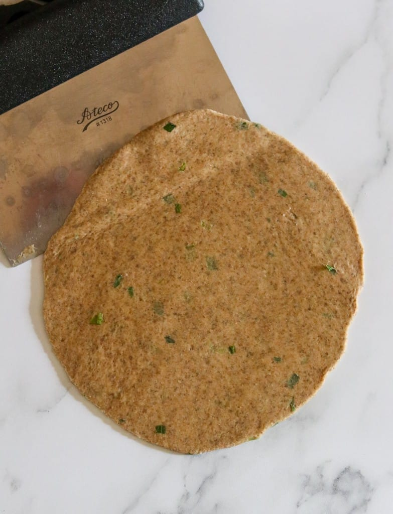 Flatbread dough rolled out on a counter with a dough scraper