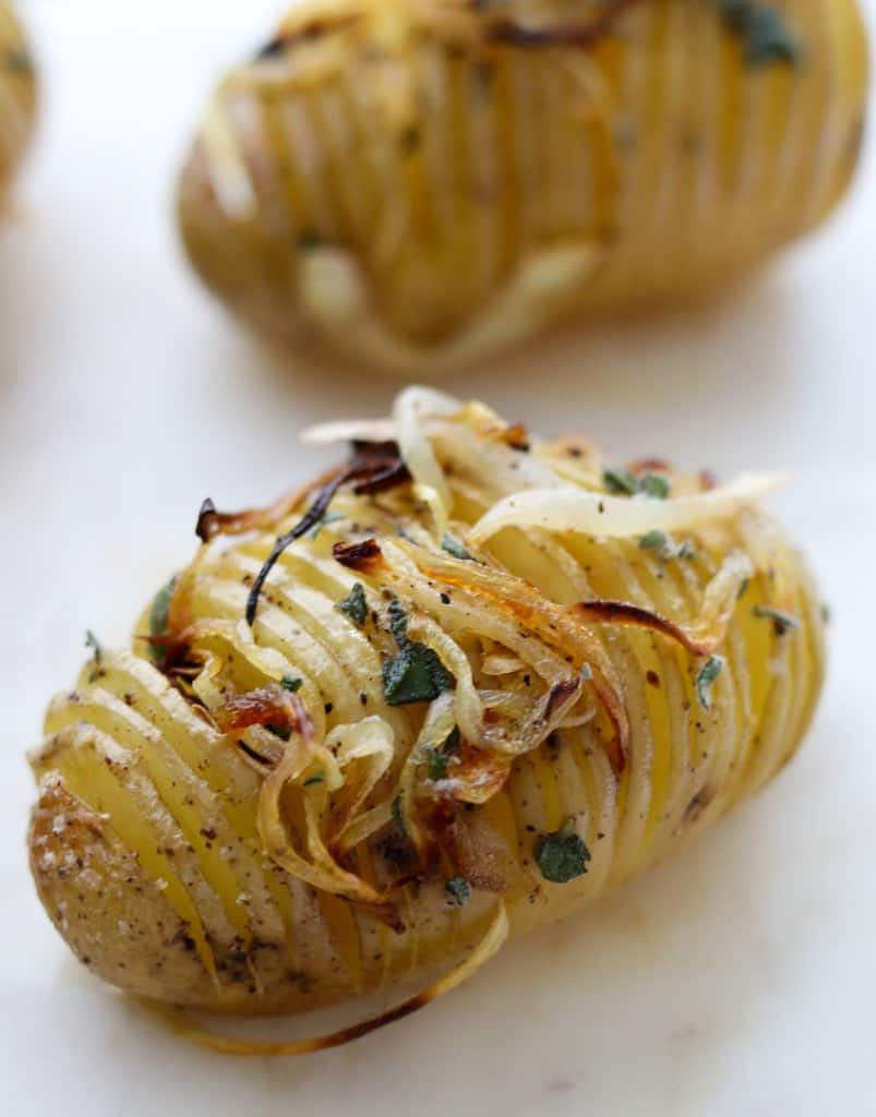 Close up of a hasselback potato topped with herbs and caramelized onions