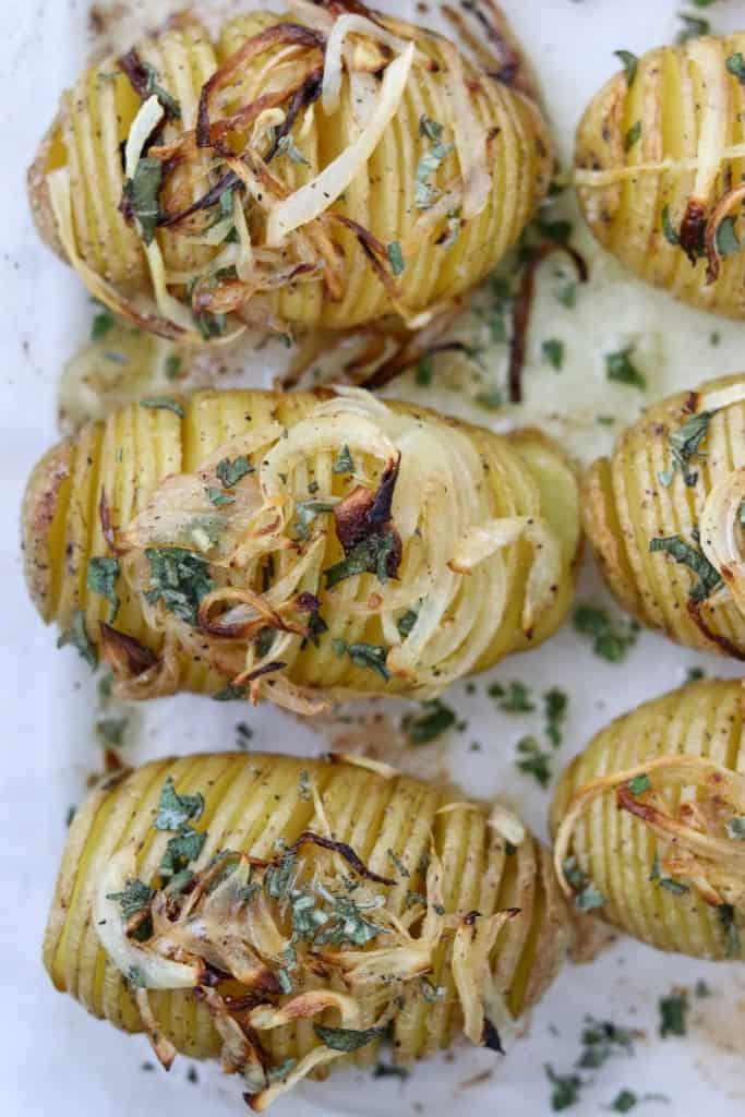 Hasselback potatoes topped with herbs and caramelized onions