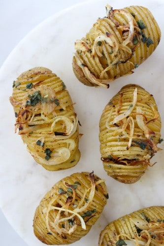 Hasselback potatoes topped with herbs and onions on a marble surface