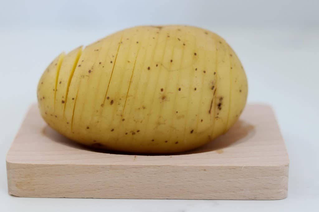 Close up of a sliced hasselback potato on a wood surface
