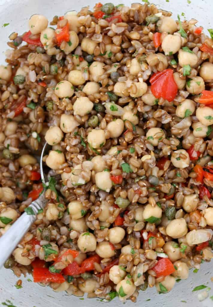 rye berries, chickpeas and roasted red peppers tossed together in a bowl with a spoon