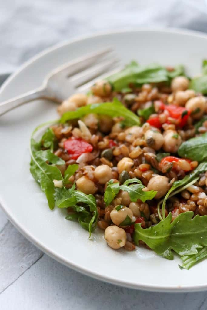 Rye berry and chickpea salad on a plate with a fork