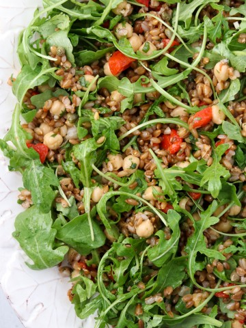 Rye berry salad with roasted peppers and arugula on a platter