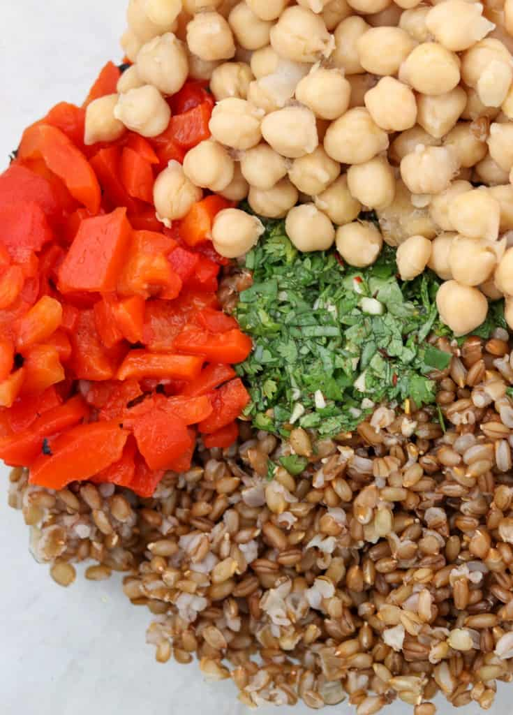 rye berries, red peppers, chickpeas and herbs in a bowl