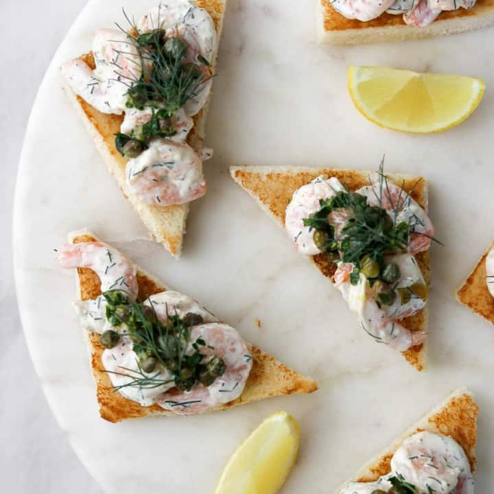Creamy shrimp salad on toast with lemon wedges on a marble plate.
