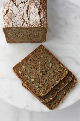 Danish rye bread sliced on a marble surface.
