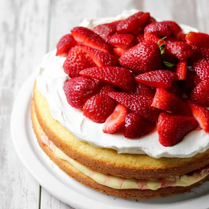 Strawberry layer cake on a wooden surface.