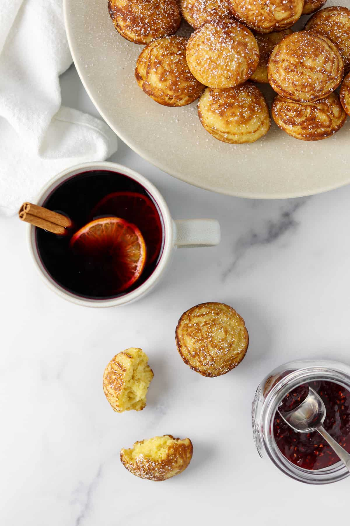 Æbleskivers, jam and mulled wine on a marble surface.