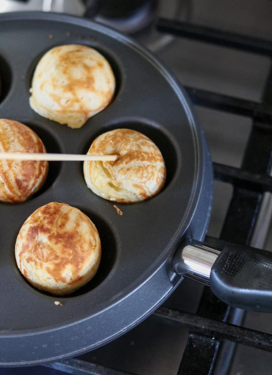 Æbleskivers in a pan with a wooden skewer.