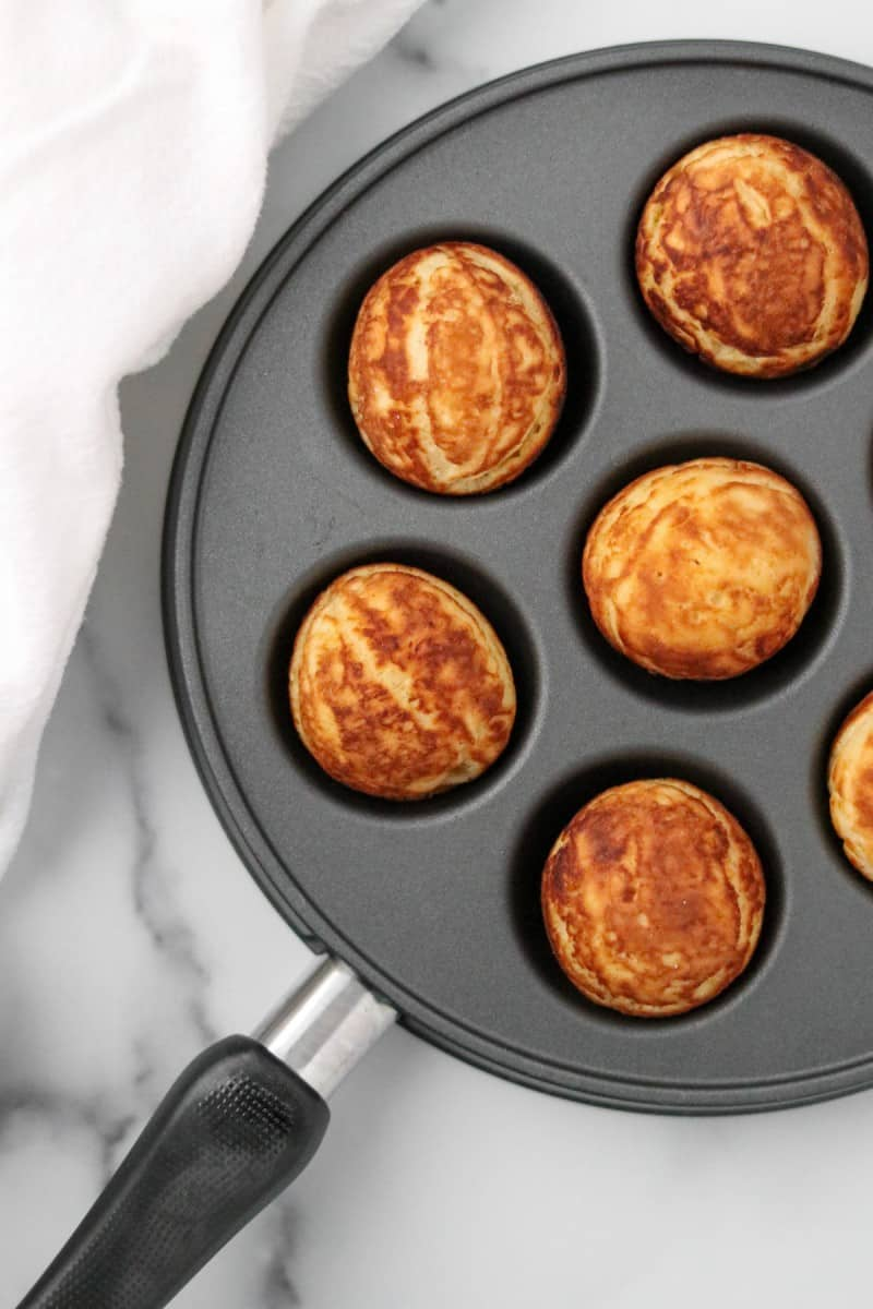 Æbleskivers in a pan on a marble surface next to a towel.