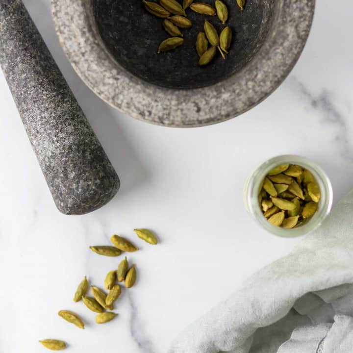 Cardamom pods on a marble surface with a mortar and pestle.