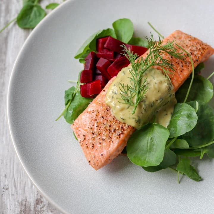 Salmon, spinach and pickled beets topped with mustard dill sauce on a plate.