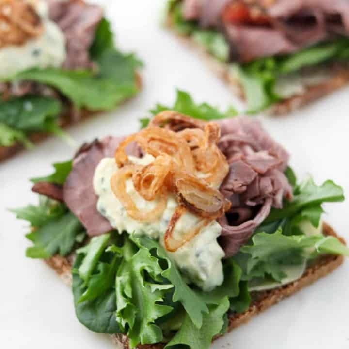 Open faced roast beef sandwich on a marble surface.