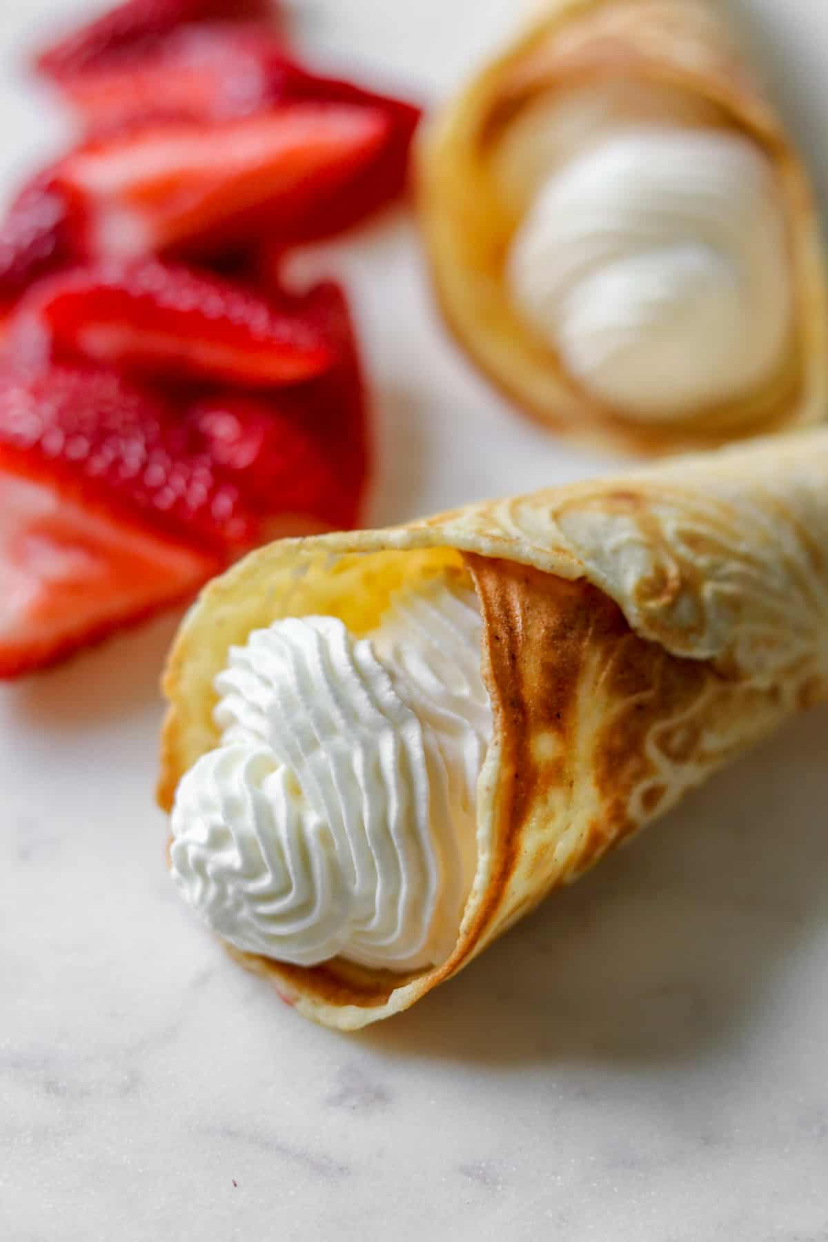 Close up of krumkake filled with whipped cream and strawberries on a plate.