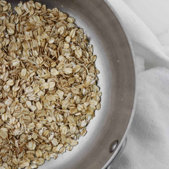 A saucepan filled with raw oats next to a napkin.