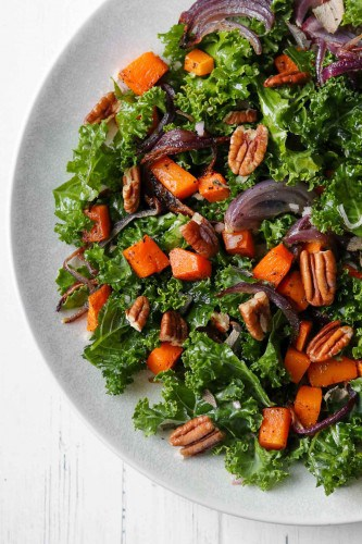 Kale salad with roasted butternut squash and pecans on a plate.