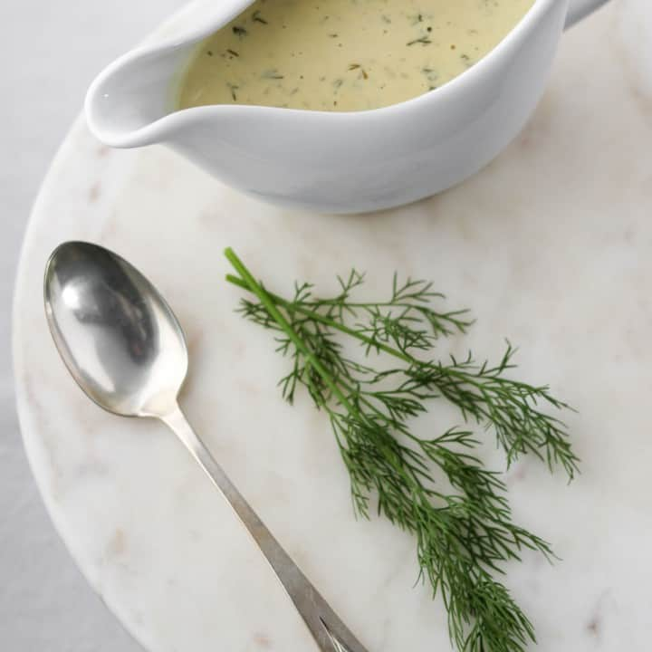 Mustard sauce in a gravy boat next to a spoon and dill sprig.