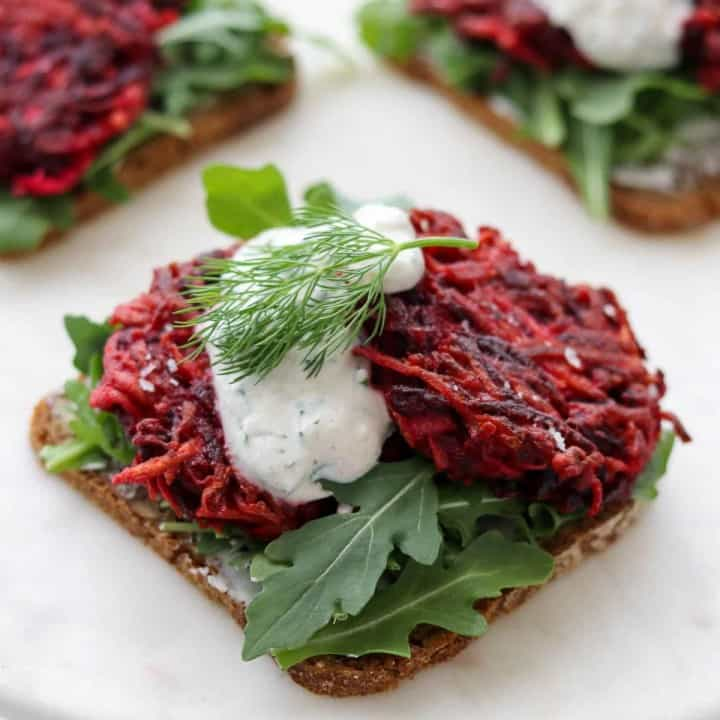 Open faced sandwich topped with lettuce and beet cakes.