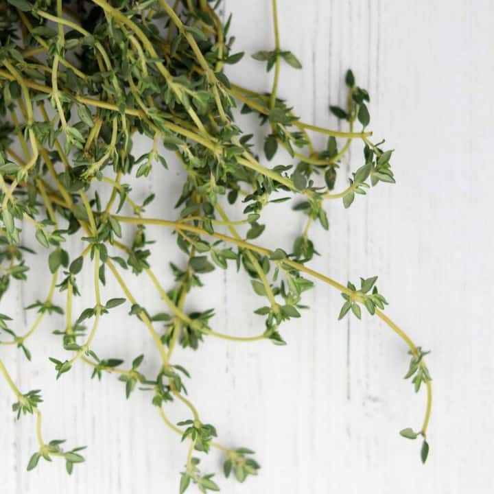 thyme sprigs on a white wooden surface.