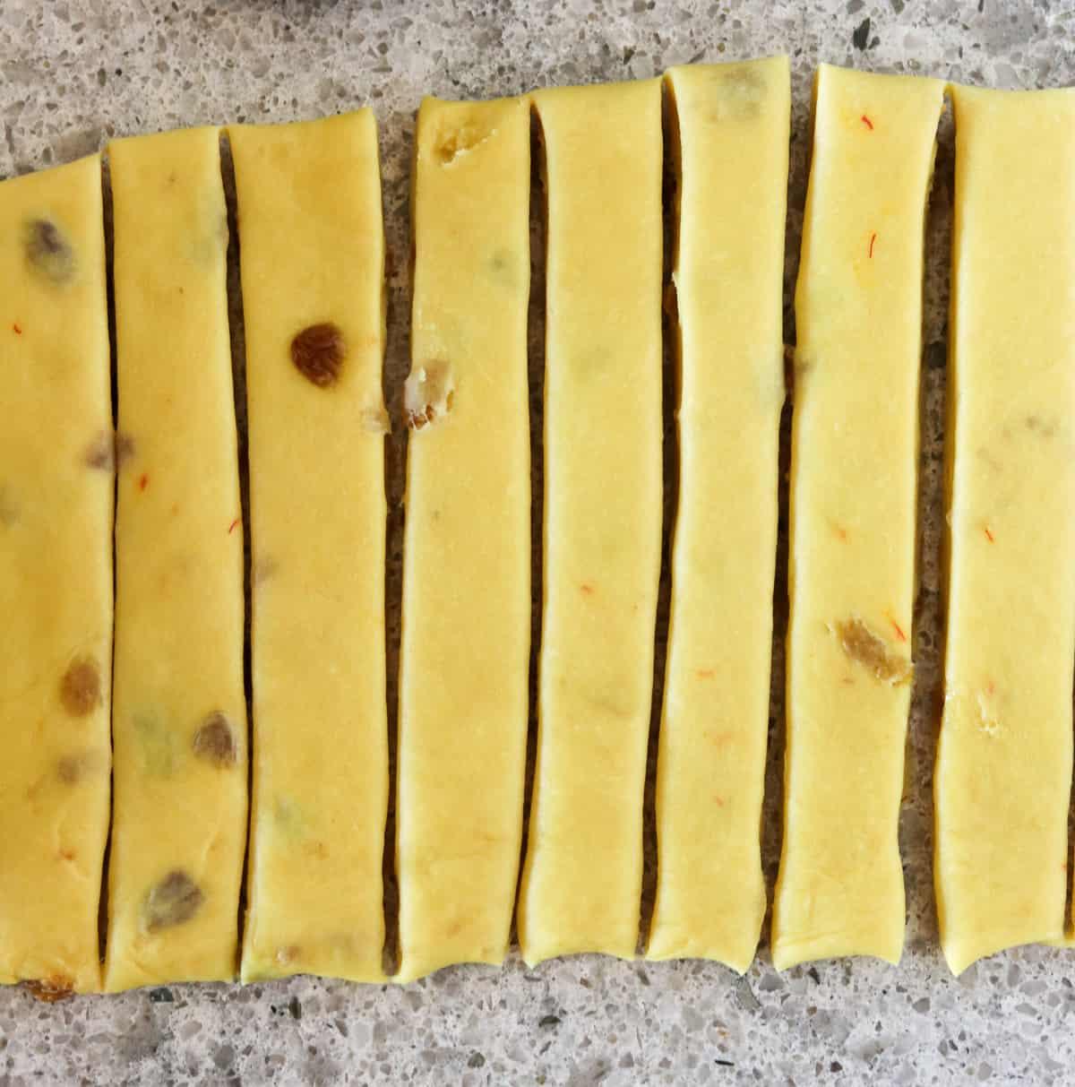 Strips of saffron dough on a gray countertop