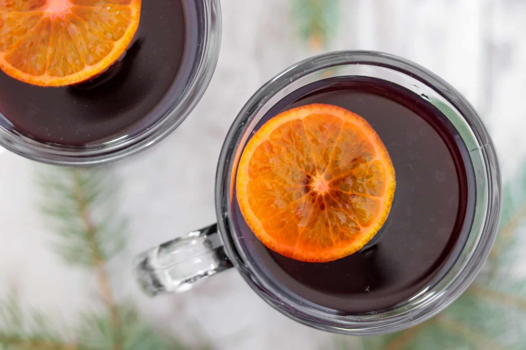 Close up of a cup of mulled wine with an orange slice floating on top.