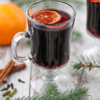 A cup of mulled wine next to evergreen branches, spices and an orange.