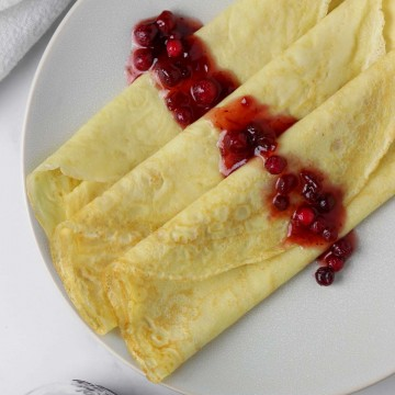 Swedish pancakes on a plate drizzled with lingonberries.