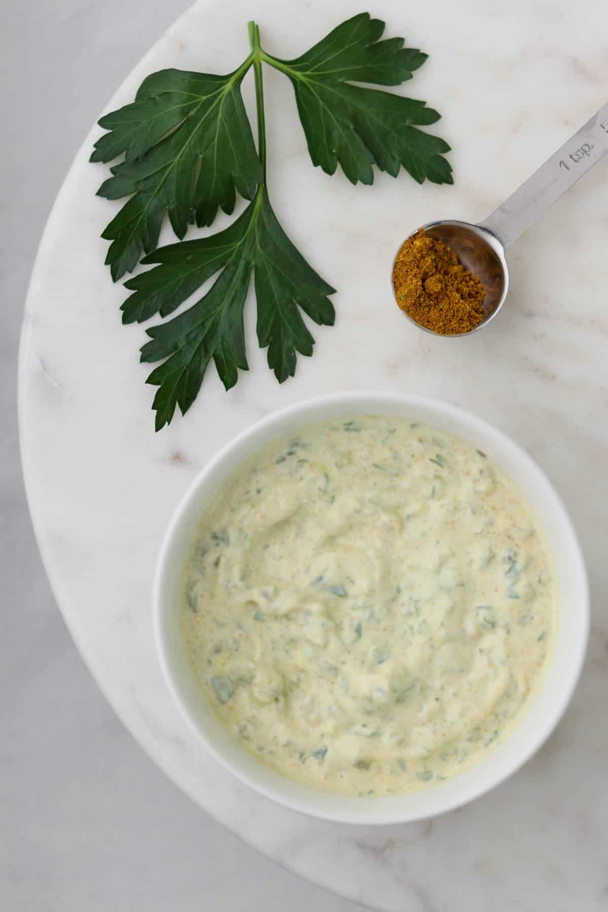 Danish remoulade in a bowl next to curry powder and parsley.