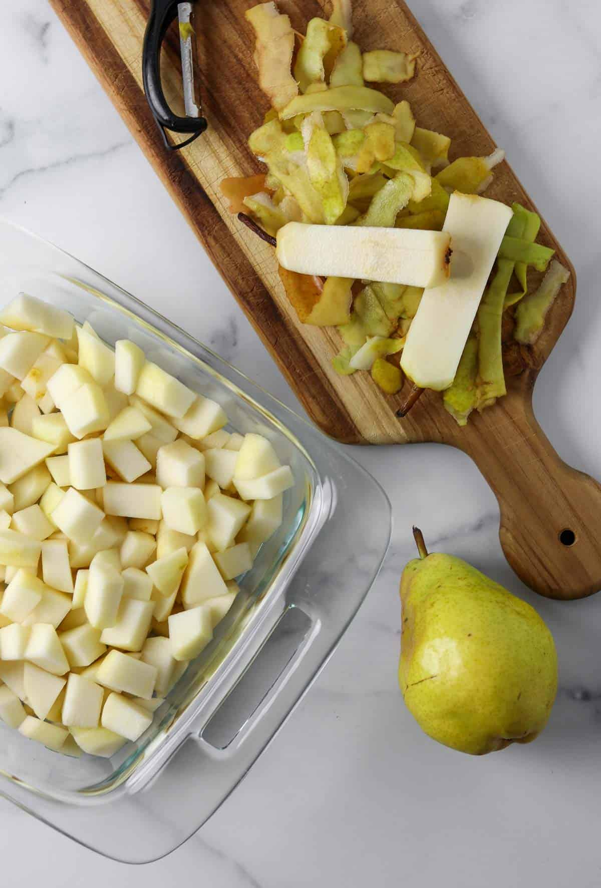 Cubed pears in a glass dish next to peels and cores and a whole pear.
