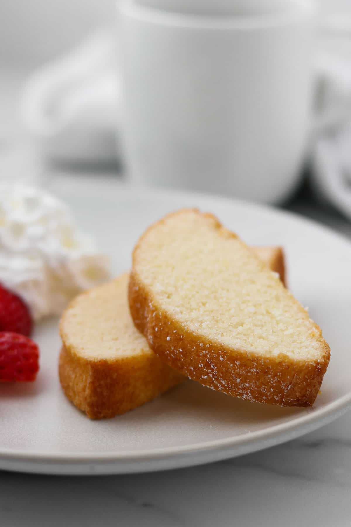 Two slices of Swedish Almond Cake on a plate next to strawberries and whipped cream.