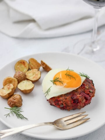 Beef Lindström on a plate topped with a fried egg next to roasted potatoes.