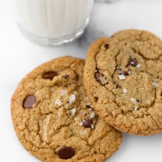 Two chocolate cookies on a marble surface next to a glass of milk.