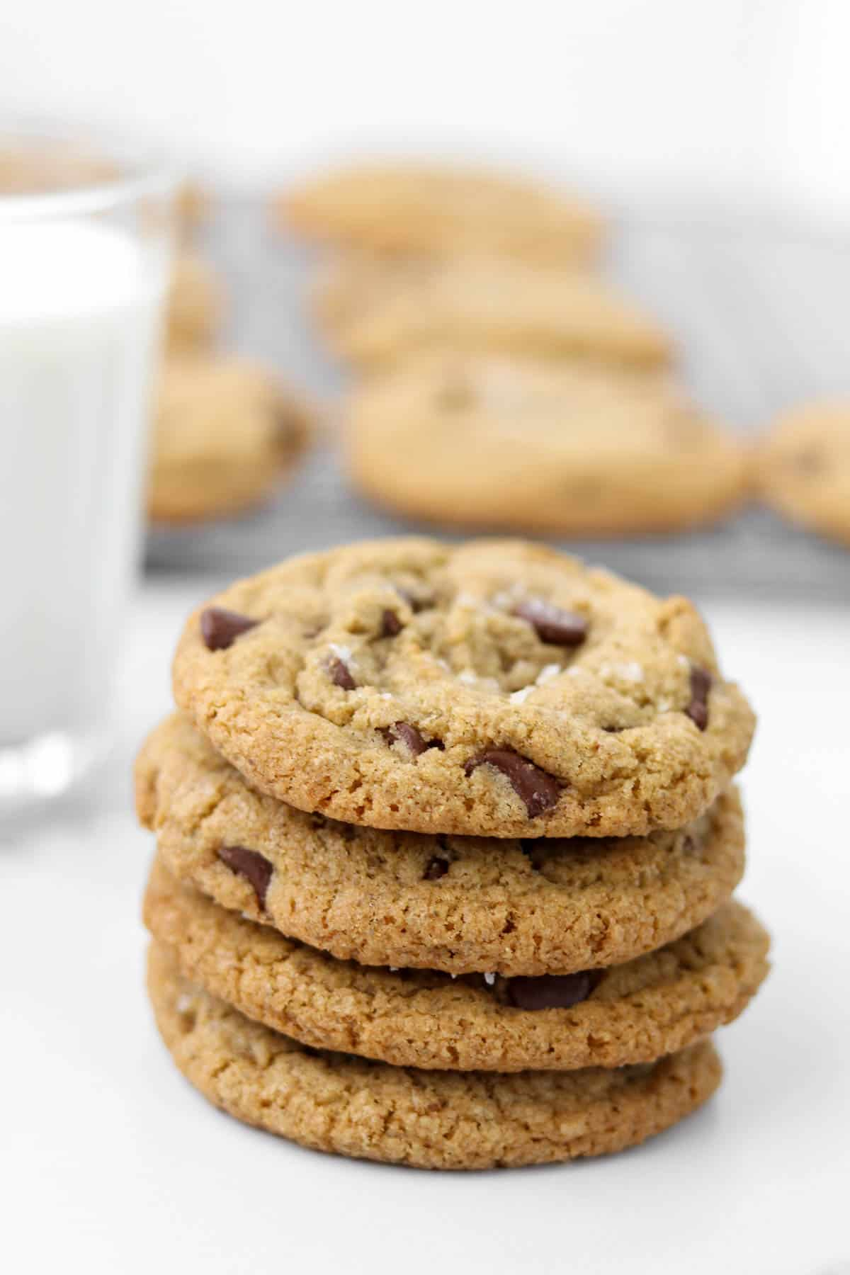 A stack of four chocolate chip cookies with a glass of milk.