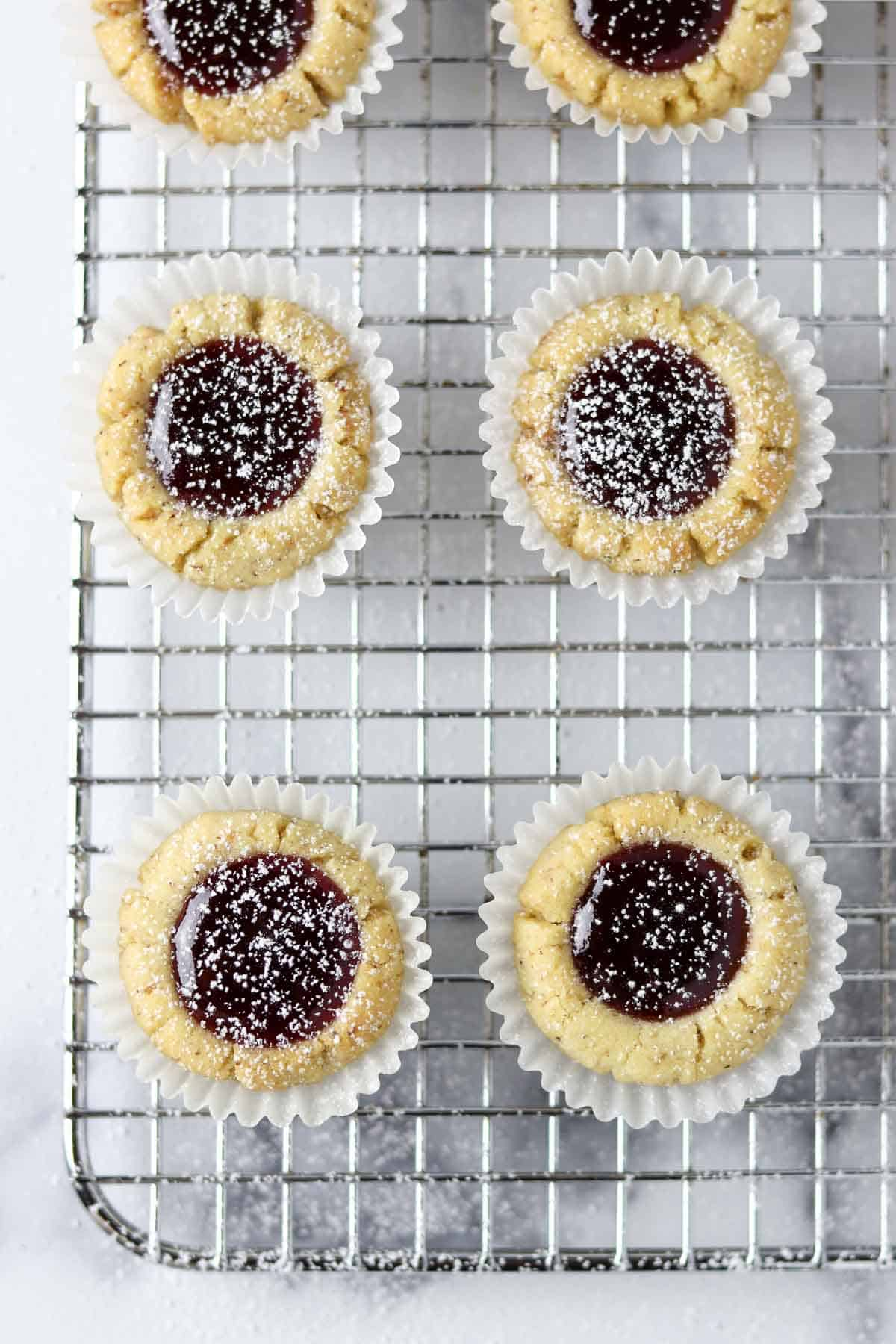 Raspberry thumbprint cookies on a cooling rack.