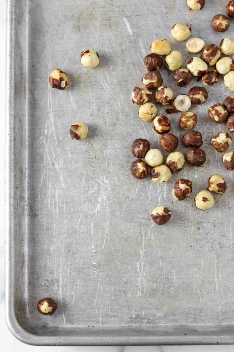 Roasted hazelnuts on a baking sheet.