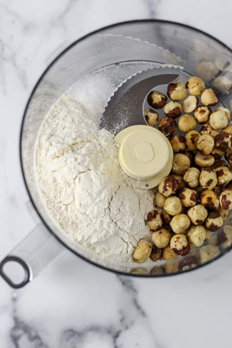 Hazelnuts, flour and salt in the work bowl of a food processor.