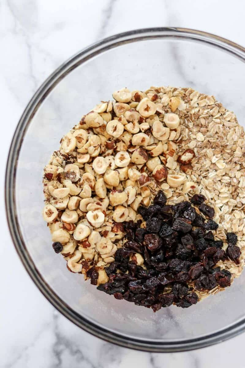 Oats, hazelnuts and dried cherries in a glass bowl.